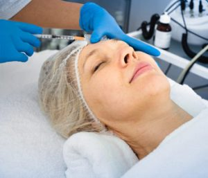 Female doctor doing beauty injection to mature woman client